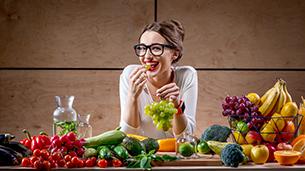 "alt=""צריכה של פירות וירקות היא בסיס חיוני לתזונה נכונה, בחורה מחייכת עם מגוון פירות וירקות"""