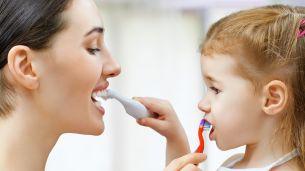 אמא וילדה מצחצחות את השיניים אחת לשניה