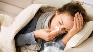 בחורה שוכבת על ספה ומקנחת את האף. התקררות VS שפעת